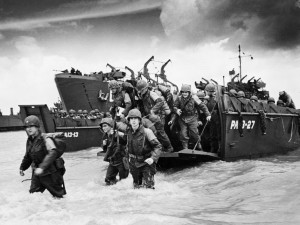 American reinforcements, arrive on the beaches of Normandy from a Coast Guard landing barge into the surf on the French coast on June 23, 1944. They will reinforce fighting units that secured the Norman beachhead and spread north toward Cherbourg.